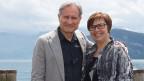 Moderator und Moderatorin stehen am Ufer des Vierwaldstättersees.