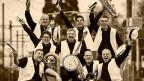 Lachende Männer einer Jazzband mit ihren Instrumenten.