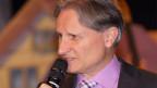 Ein Moderator in grauer Weste und mit Mikrofon.