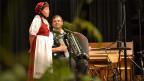 Eine junge Jodlerin wird bei ihrem Auftritt von einem Akkordeonisten begleitet.