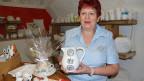 Eine Frau zeigt in einem Keramik-Atelier einen verzierten Krug.