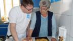 Reporter und Köchin stehen in einer Küche und begutachten ein fertiges Ofengericht.