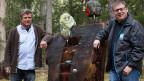 Zwei Männer stehen im Wald neben einer Skulptur aus Holz.