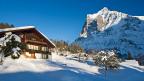 Eine Hütte in einer verschneiten Berglandschaft.