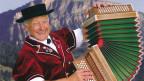 Ein Mann mit Hut spielt Akkordeon.
