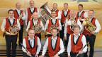 Eine Blasmusikformation mit Musikanten, die weisse Hemden und rote Gilets tragen.