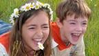 Ein Mädchen und ein Knabe liegen fröhlich lachend im Gras.