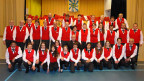 Gruppenbild mit Blasmusikantinnen und -musikanten in rot-weiss-schwarzen Uniformen.