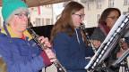 Drei Klarinettistinnen mit Mützen und dicken Jacken.