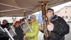 Blasmusikanten in dicken Jacken während eines Konzerts im Schneetreiben.