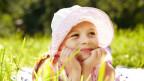 Mädchen mit Hut auf Sommerwiese.