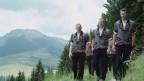Mitglieder vom Jodlerklub Wiesenberg marschieren auf einen Berg.