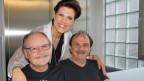 Lucky Boys auf Bank mit Maja Brunner im Hintergrund.