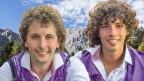 Zwei junge lachende Männer vor einer Bergkulisse.