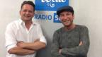 Martin Marcell und Freddy März stehen lachend vor dem blau-weissen Logo von SRF Musikwelle.
