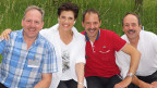 Gruppenbild mit drei Männern und einer Frau, die auf einer Mauer in einem Garten sitzen.