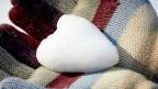 Ein aus Schnee geformtes Herz liegt in behandschuhten Händen.