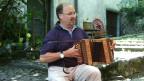 Ein Mann sitzt im Freien und spielt Schwyzerörgeli.