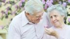 Seniorenpaar bewundert lila Blüten eines Baums.