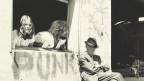 Zwei junge Menschen blicken von einem Fenster aus auf einen alten Mann, der auf einem Stuhl sitzt.