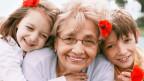 Eine Oma zwischen ihren beiden Enkelkindern.