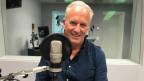 Ein Mann sitzt aufrecht hinter einem Mikrofon in einem Radiostudio.