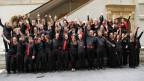 Junge Chorsängerinnen und -sänger posieren für ein Gruppenfoto vor einer Treppe.
