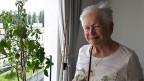 Eine ältere Frau mit grauen Haaren und bedrucktem T-Shirts schaut zufrieden aus dem Fenster.