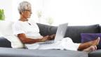 Seniorin auf Sofa mit Laptop.