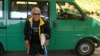 Ein älterer Mann in Sportbekleidung vor einem grünen Kleinbus.