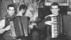 Schwarz-Weiss-Fotografie mit zwei Akkordeonisten und einem Klavierspieler.