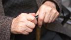 Hände eines alten Mannes auf einem Gehstock.