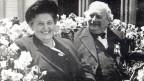 Alte Schwarz-Weiss-Fotografie mit einem Ehepaar während einer Kutschenfahrt.