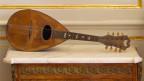 Eine Mandoline liegt seitlich auf einer antiken Kommode.