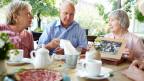 Ein älterer Mann und zwei ältere Frauen beim Kaffeetrinken.