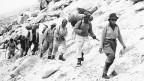 Eine Bergsteigerin gefolgt von einer Gruppe von Männern in einer felsigen Landschaft.