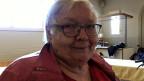 Eine ältere Frau mit Brille, rotem Pullover und roter Jacke blickt verschmitzt in die Kamera.