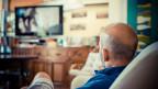 Ein Mann sitzt auf dem Sofa und schaut fern.