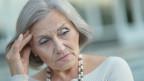 Eine ältere Frau stützt gedankenverloren ihren Kopf auf die Hand.