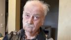 Ein alter nachdenklicher Mann mit grauen Haaren und Schnurrbart.