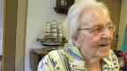 Seniorin sitzt an Tisch im Altersheim.