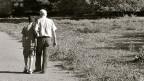 Schwarz-Weiss-Fotografie von einem Grossvater, der mit seinem Enkel spazieren geht.