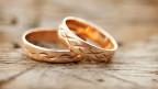 Zwei goldene Eheringe auf einem Holztisch.