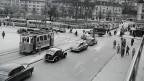 Schwarz-Weiss-Fotografie von einer belebten Stadt mit alten Autos und Trams.