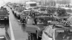Schwarz-Weiss-Fotografie mit unzähligen Autos, die im Stau stehen.
