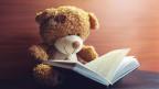 Ein Plüsch-Teddybär mit fröhlichen Knopfaugen sitzt vor einem aufgeschlagenen Buch.