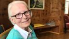Eine ältere Frau mit weissen Haaren und Brille in einem Wohnzimmer.