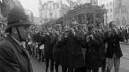 Basler Fasnachtscliquen marschieren auf der Strasse. Im Hintergrund ein altes Tram.
