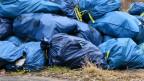 Blaue Müllsäcke liegen wild herum.