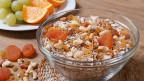 Ein mit Frühstücksflocken und Früchten gefüllte Schälchen.